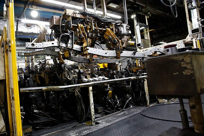 クレーンゲーム機のようなアームで運ばれるメインフレーム。この後クロスメンバーが溶接されラダー(梯子)状になっていく