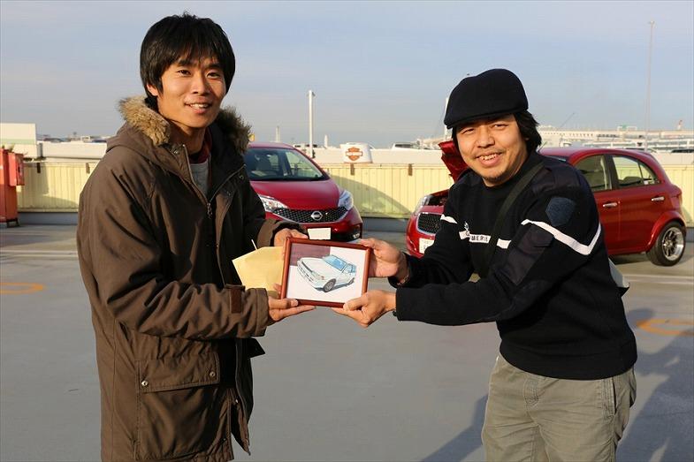 遠藤イヅルさんから愛車、カローラFXが書かれたイラストを受け取る五十嵐さん