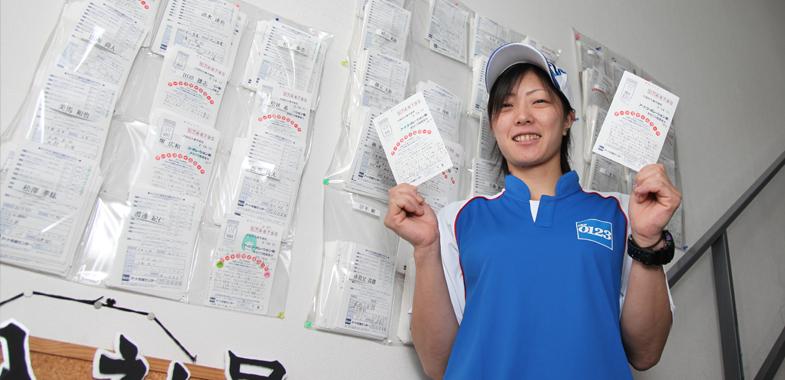 伊部さん宛てのスマイルカードを両手に持ちパチリ。約5年前の繁忙期に、回収率とCSで1位をとったことも