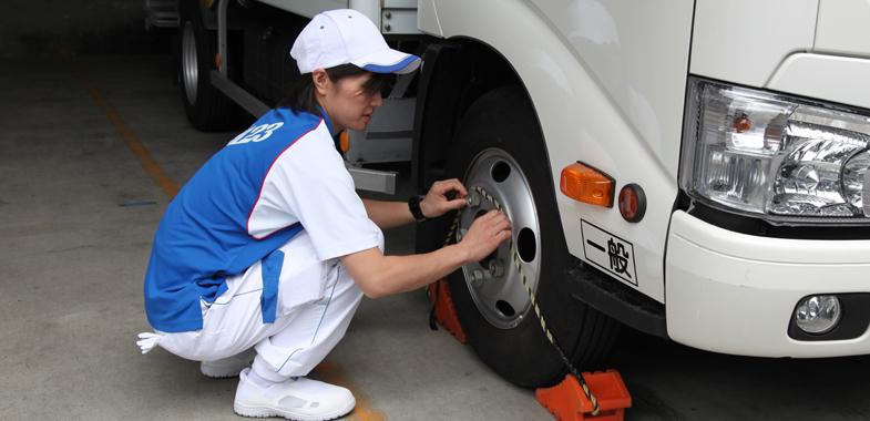 駐車中は輪止めでタイヤを挟むのがルール。足を引っ掛けないように、ていねいにロープをホイールナットにかけます