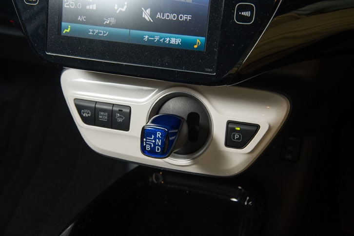 シフトセレクター(写真中央の青いレバー)の周辺には、走行モード切り替えなどの各種スイッチが備わる。一番左は「HV/EV切り替えスイッチ」で、長押しすると、ハイブリッド走行と充電を同時に行う「バッテリーチャージモード」を選択できる。