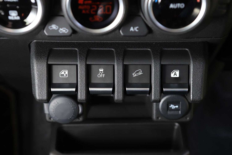 センタークラスターに備わる「ヒルディセントコントロール」の操作スイッチ(右から2番目)。新型「ジムニー/ジムニーシエラ」には、このほかにも空転するタイヤに自動でブレーキをかけ、ぬかるみなどからの脱出をアシストするブレーキLSD機能なども用意されている。