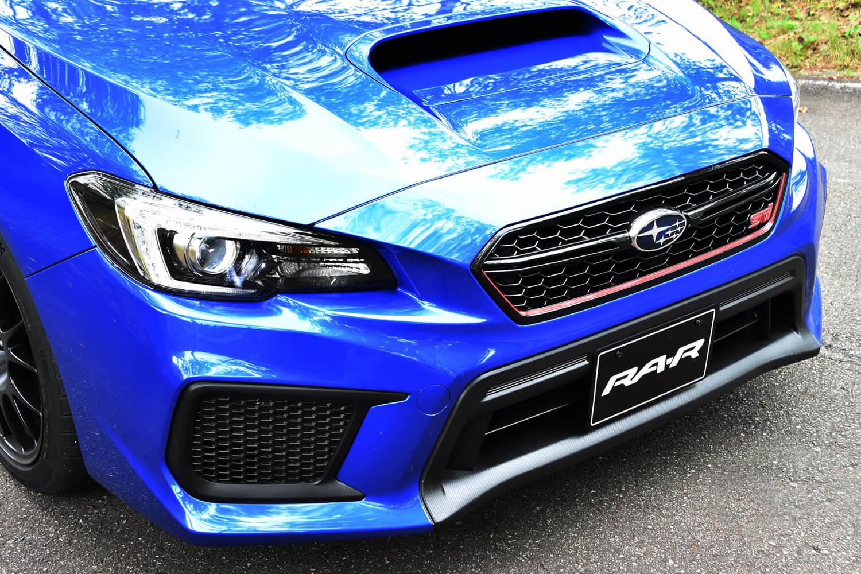 パワープラントやシャシーに施された大幅な改良とは裏腹に、デザイン面でのベース車との差別化は控えめ。フロントまわりでの違いは、チェリーレッドのストライプとSTIのエンブレムがあしらわれたメッシュグリル程度である。