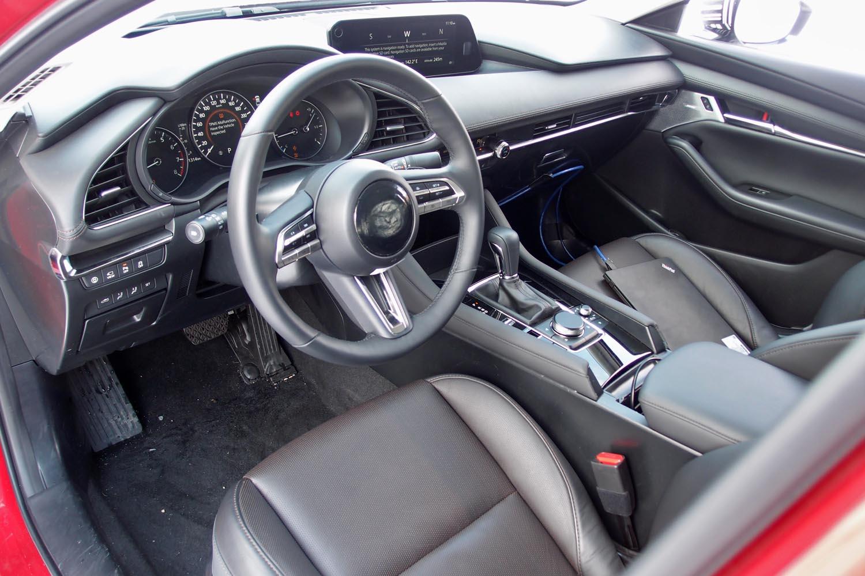 """試乗車「マツダ3セダン」(北米仕様車)のインテリア。テスト用のため仕立てに未完成なところもあるものの、ゆるやかなラインが交差する、""""囲まれ感""""のあるデザインが見てとれる。"""