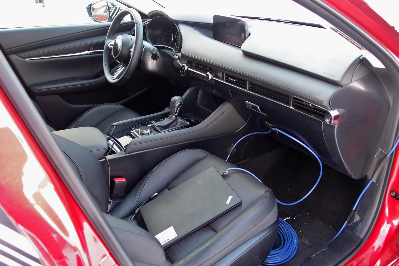 「GVCプラス」のテストは、運転中に助手席の開発スタッフがPC(写真手前)を使って制御のオンオフを切り替える方式で実施。車両の乗り換えをしないおかげで、その効果がより明確に体感できた。なお、量産型の「マツダ3」は全車GVCプラスを標準装備。スイッチなどでオフにすることはできない。