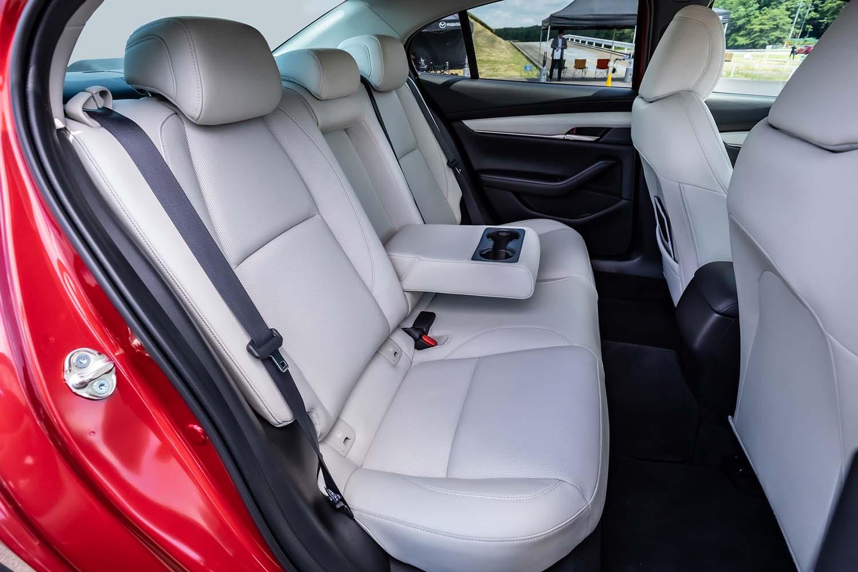 「セダン」のリアシート。ドア形状が異なっているため「ファストバック」に比べて乗り降りはしやすいが、マツダの発表数値によればセダンのショルダールームはファストバックより3mm広いだけで、両車の居住性にほとんど差はない。後席背もたれはセダン、ファストバックとも6:4分割可倒式を採用している。