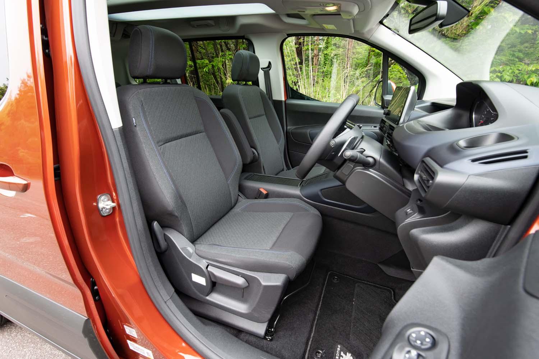 シート表皮はざっくりとしたグレーのファブリック。前席には収納可能なセンターアームレストが備わる。