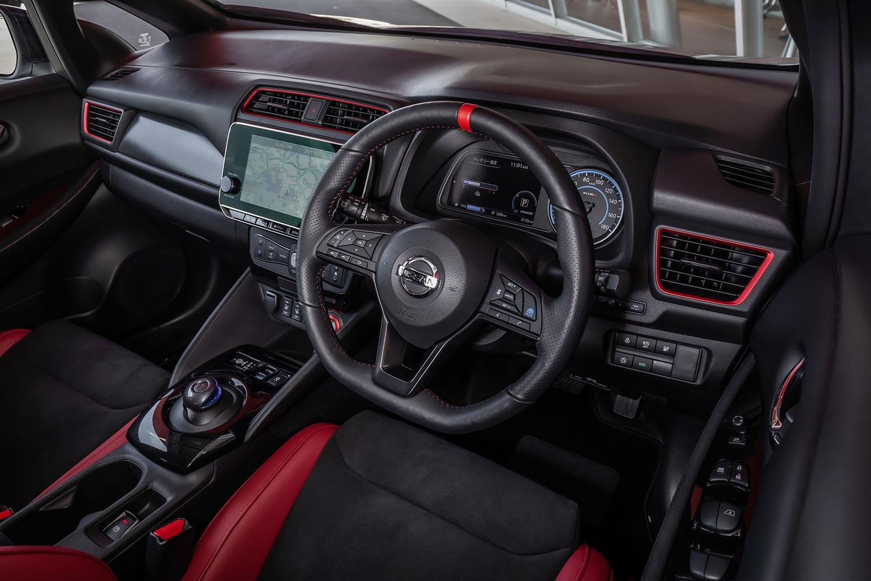 12時の位置にレッドのセンターマークが付く本革のステアリングホイール(写真)はオプションアイテム。エアコン吹き出し口やパワースイッチにあしらわれたレッドの加飾や、ダッシュボードに施されたカーボン調のパネルが「リーフNISMO」のインテリア上の特徴となっている。